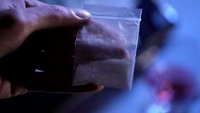 男性举行的白色粉末包裹,工业制药,非法药物贸易 免版税库存照片