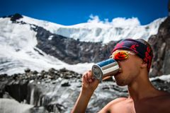 男性从一个杯子的登山家饮用水在山旅行生活方式概念冒险激活假期extre的冰川 免版税库存图片