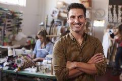 男性企业主在衣物设计演播室,横渡的胳膊 免版税库存照片