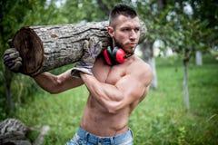 男性伐木工人英俊的人切口树和移动的日志 免版税库存照片