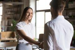 男性作嘘声与促进的握手激动的女性雇员问候 免版税库存图片
