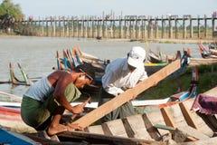 男性修理传统小船 免版税库存图片