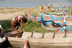 男性修理传统小船 免版税库存照片