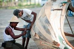 男性修理传统小船 库存照片