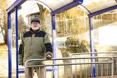 男性前辈在公共汽车站等待 免版税库存图片