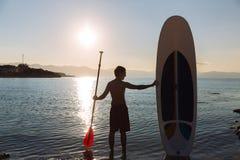男性剪影与一口海浪和桨的在海洋的手上 概念生活方式,体育 免版税库存图片