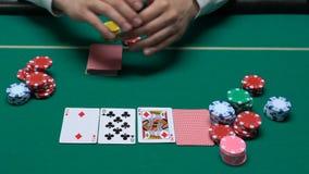 男性副主持人在赌博娱乐场成交了做赌注,扑克牌游戏的卡片和等待的球员 股票视频