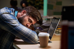 男性办公室工作者睡着在后研究膝上型计算机的书桌 库存照片