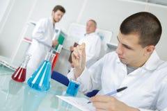 男性医学实验室年轻研究员执行测试与蓝色液体 免版税库存图片