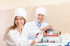 男性医生和护士做验血 免版税库存照片
