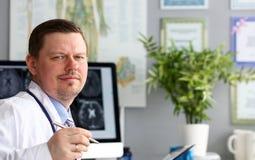 男性医生在看在照相机微笑的办公室 免版税图库摄影