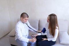 男性医生测量女性患者压力有tonometer的w 免版税库存图片