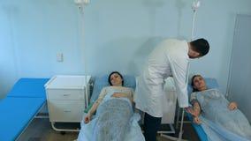 男性医生谈话与休息在医院病房里的滴水的女性患者 库存照片