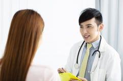男性医生谈话与妇女患者 库存图片