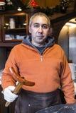 男性卖主厨师用在厨房的德国香肠 库存图片