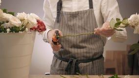 男性卖花人递特写镜头,裁减为在花店的花束上升了 在花卉设计演播室供以人员助理或所有者,做 股票录像