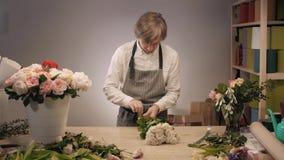 男性卖花人递特写镜头,裁减为在花店的花束上升了 在花卉设计演播室供以人员助理或所有者,做 股票视频