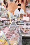 年轻男性卖主提供的土豆 库存图片