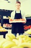 男性卖主运载的箱子柿子 库存图片