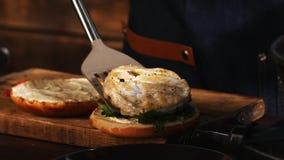 男性厨师特写镜头加在一个油煎的汉堡包小圆面包的蓝色围裙的鲜美和水多的鸡肉 E 股票录像