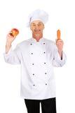 男性厨师用苹果和红萝卜 免版税库存图片