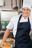 男性厨师藏品被烘烤的蛋糕在厨房里 库存图片