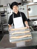 男性厨师陈列被烘烤的面包大面包 免版税库存图片