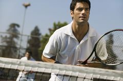 男性双等待服务正面图的网球员集中于前景 库存图片