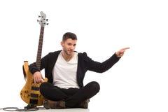 男性吉他弹奏者坐地板和指向 库存图片