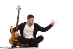 男性吉他弹奏者坐地板和指向 免版税图库摄影