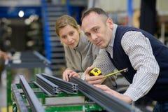 男性和女工在金属制品工厂 免版税库存照片
