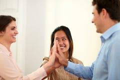 男性和女性同事挤作一团他们的手 免版税图库摄影