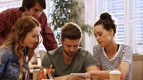 男性和女性商业主管谈论在数字式片剂在他们的书桌