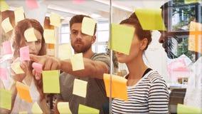 男性和女性商业主管谈论在数字式片剂,当读稠粘的笔记时