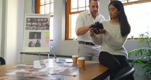 男性和女性图表设计师谈论在数码相机4k 股票录像