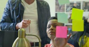男性和女性图表设计师谈论在稠粘的笔记4k 影视素材