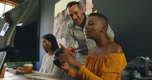 男性和女性图表设计师谈论在计算机在书桌4k 影视素材
