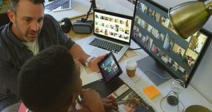 男性和女性图表设计师谈论在计算机4k上的照片 股票视频