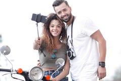 男性和女性小型摩托车的在镇 免版税库存图片