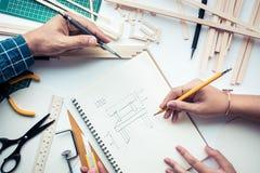 男性和女性工作在有木材料的工作台 DIY 免版税库存图片