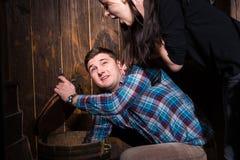 年轻男性和女性打开了桶和设法解决conu 免版税库存图片
