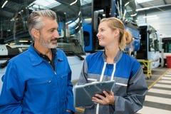 男性和女性技工谈话在公交车站 免版税图库摄影