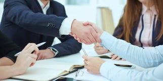 男性和女性握手在现代办公室 严肃的企业和合作概念 伙伴做成交,密封与 库存照片