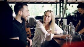男性和女性朋友在坐在一个酒吧柜台的自助食堂在与男服务员工作的夏日 美好女孩知道 影视素材