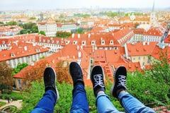 男性和女性腿在布拉格市捷克共和国屋顶背景中在一个晴朗的夏日 典型的布拉格 库存图片