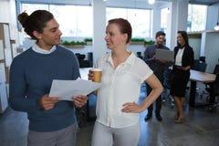 男性和女性董事谈论在文件 免版税图库摄影