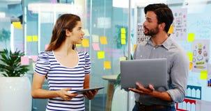 男性和女性董事谈论在电子设备 股票视频