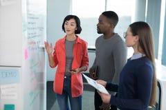 男性和女性董事谈论在whiteboard 免版税图库摄影
