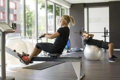 男性和女性解决在健身房 免版税库存图片
