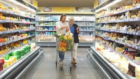 男性和女性顾客推挤有杂货产品的推车在超级市场走道 影视素材